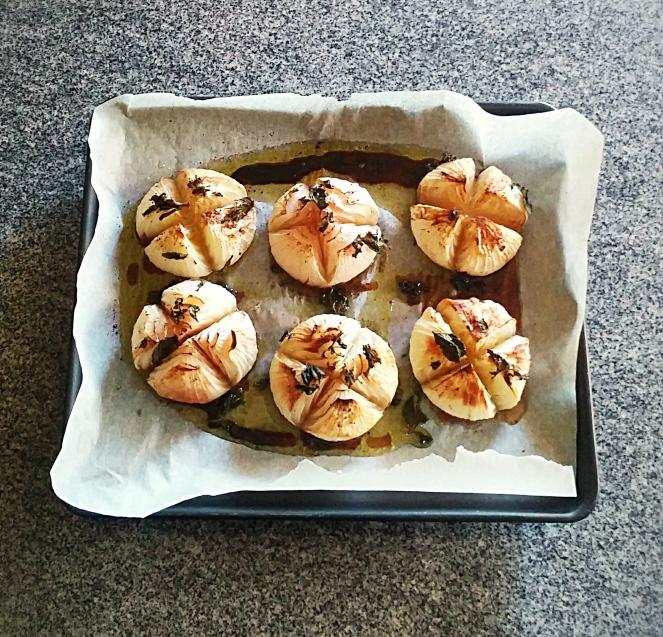 Cipolle fresche bianche cotte al forno con foglioline di menta.