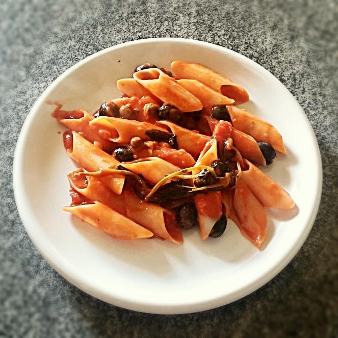 Un goloso piatto di pasta glutenfree con sugo piccante di pomodori pachino capperi e olive nere
