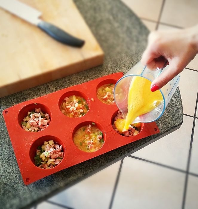 Riempimento degli stampi in silicone con i vari ingredienti: cacio, prosciutto cotto, asparagi, erba cipollina e uova sbattute.
