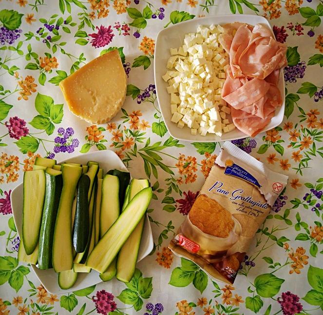 Parmigiano reggiano, mozzarella, mortadella Bologna, zucchine e pan grattato glutenfree sono gli ingredienti necessari alla preparazione della parmigiana di zucchine senza glutine