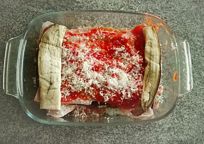 Composizione degli strati di melanzana alla parmigiana all'interno di una pirofila.