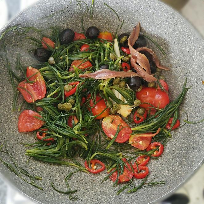 La barba dei frati viene saltata in padella con aglio, peperoncino, acciuga, capperi, olive, e pomodorini datterini.