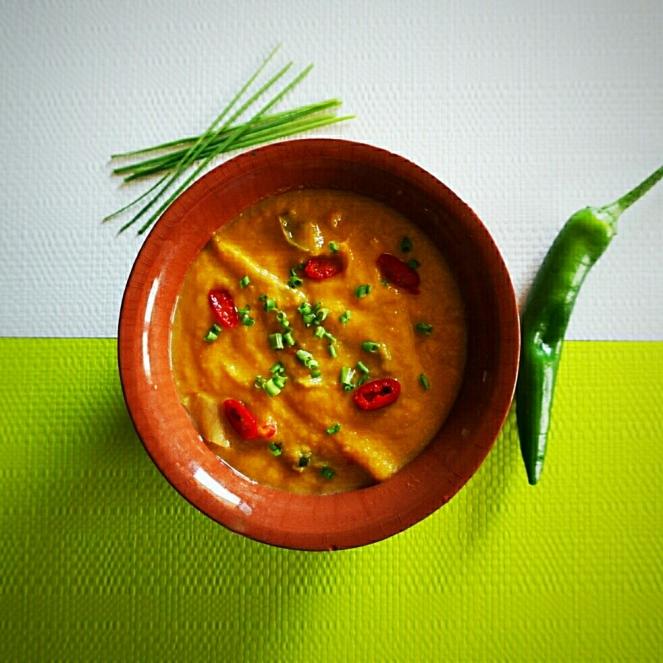 Zuppa esotica pronta e servita con erba cipollina.