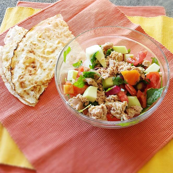 La nostra insalata di cetriolo carosello, pomodoro cuore di bue, cipollotti, tonno e rucola accompagnata da pane guttiau senza glutine.