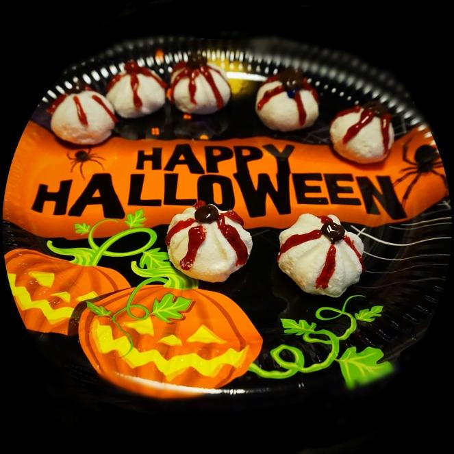 Occhi sanguinolenti di meringa per la sera di Halloween, ottenuti decorando le meringhe con ldel colorante alimentare per dolci al sapore di fragola e cioccolato.